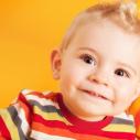 Un garçon devant un fond jaune-orangé