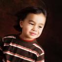 Un garçon photographiant devant un fond foncé