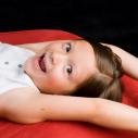 Une jeune fille couchée sur un grand coussin rouge et souriante
