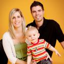 Une famille de trois devant un fond jaune/orangé