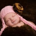 Un bébé portant une tuque rose et une fleur dorée